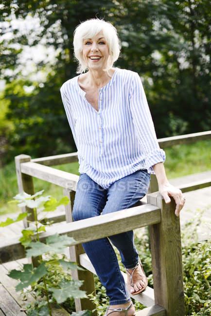 Портрет посміхаючись білим волоссям старший жінка, що сидить на дерев'яних перил — стокове фото