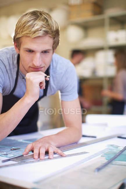 Молодий чоловік у майстерні вітражі для виробництва — стокове фото