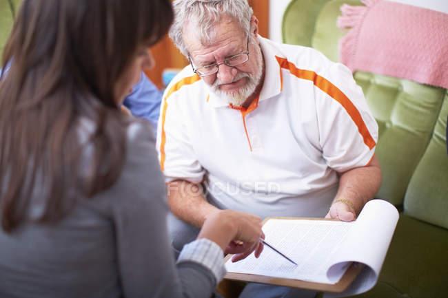 Woman explaining document to senior man — Stock Photo