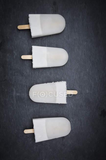 Fila de paletas de coco en la superficie negra - foto de stock