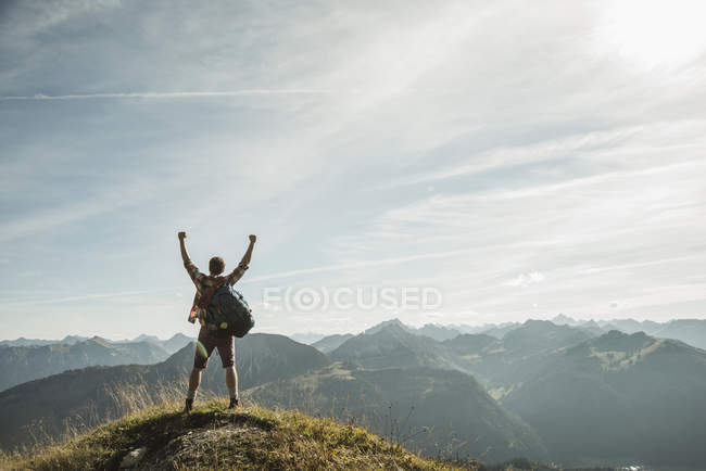 Austria, Tyrol, Young man cheering on mountain top — Stock Photo