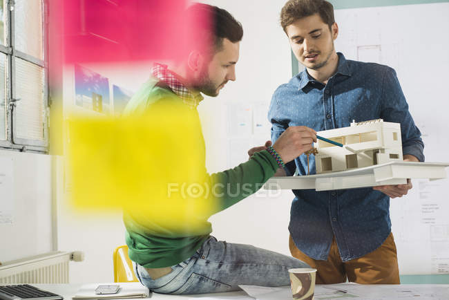 Two young architects in office discussing architectural model — Stock Photo