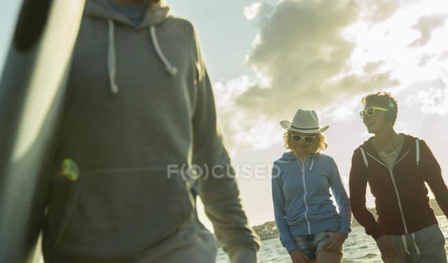 Three teenagers walking on the beach at evening twilight — Stock Photo