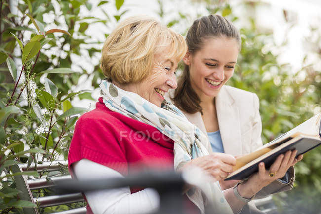 Granddaughter and her grandmother watching photo album — Stock Photo