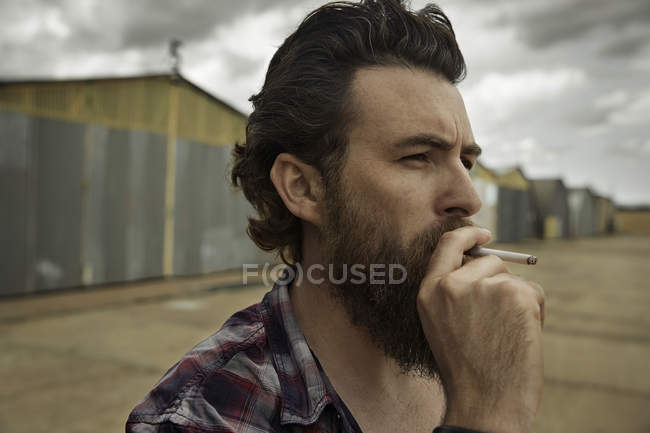 Man with full beard smoking cigarette — Stock Photo