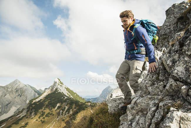 Austria, Tyrol, Tannheimer Tal, young man hiking on rock — Stock Photo