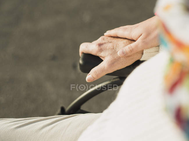 Mão de mulher jovem na mão de mulher idosa sentada em cadeira de rodas — Fotografia de Stock