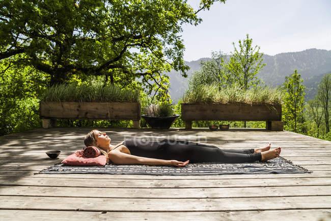 Woman lying on wooden terrace meditating — Stock Photo