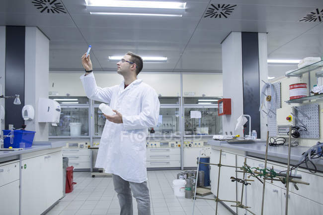 Chemist looking at test tube in lab — Stock Photo