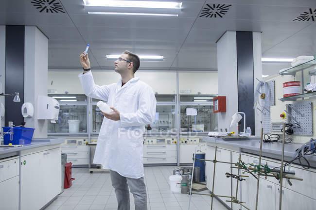 Chimiste en regardant tube à essai en laboratoire — Photo de stock