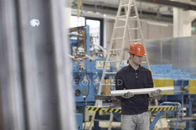 Young technician carrying pipes in industrial hall — Stock Photo
