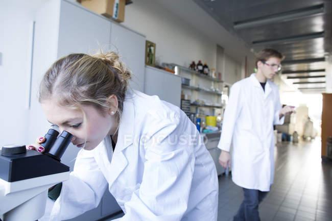 Jeune chimiste utilisant un microscope dans un laboratoire chimique — Photo de stock