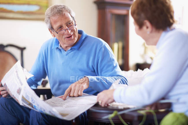 Senior mit Zeitung zu Hause im Gespräch mit Ehefrau — Stockfoto