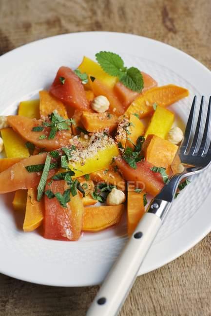 Тыква, сладкий картофель Айва салат с фундуком и свежей нарезанной зеленью, служил на плите с вилкой — стоковое фото