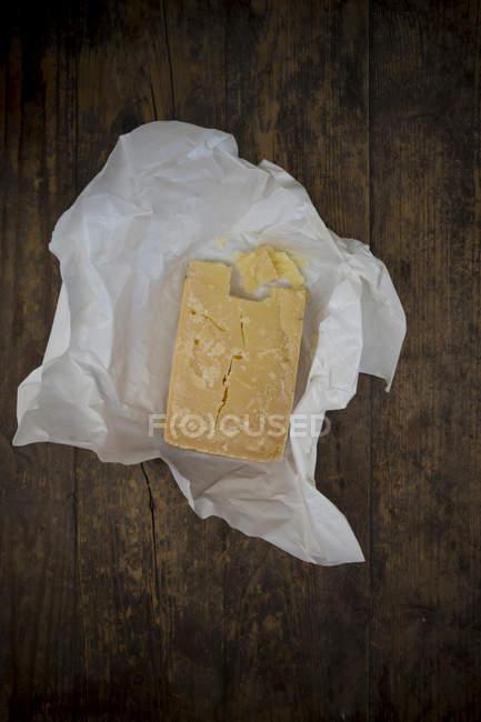 Stück von Asiago Stagionato auf Pergamentpapier und dunkles Holz — Stockfoto