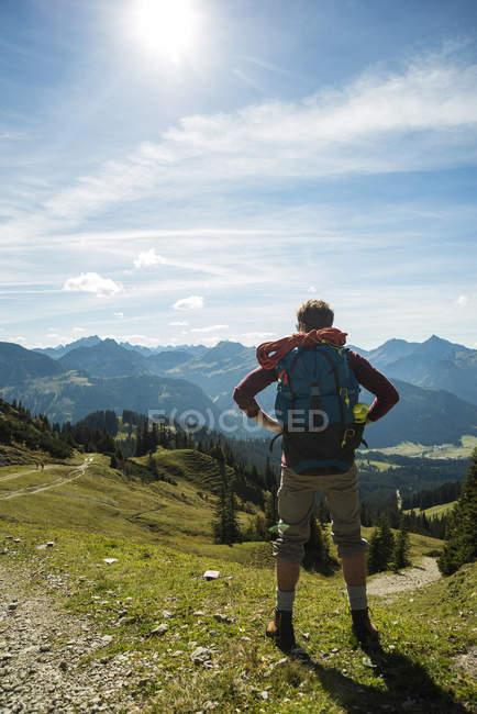 Austria, Tirolo, Tannheimer Tal, giovane in montagna guardando in vista — Foto stock