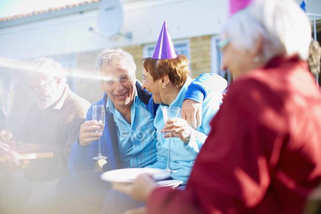 Старшие друзья на дне рождения в саду — стоковое фото