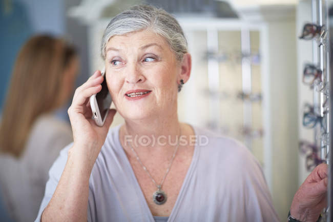 Senior woman at the optician talking on cell phone — Stock Photo