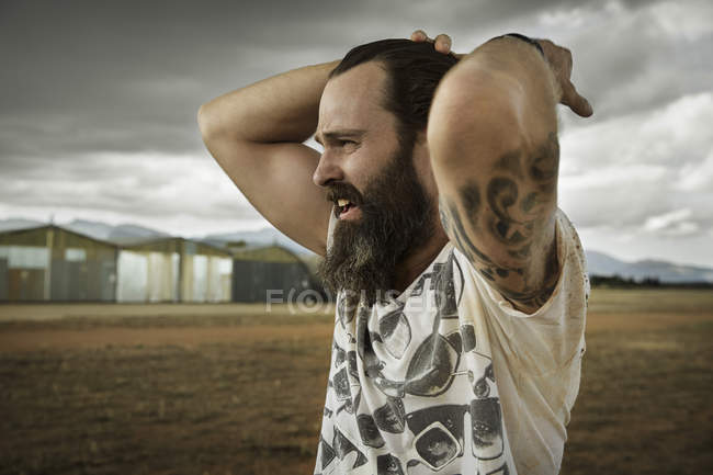Человек с бородой в заброшенном пейзаже — стоковое фото
