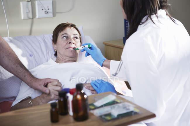 Médico examinando a mujer mayor acostada en cama de hospital - foto de stock
