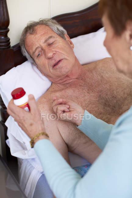 Mulher idosa cuidando do marido doente em casa — Fotografia de Stock