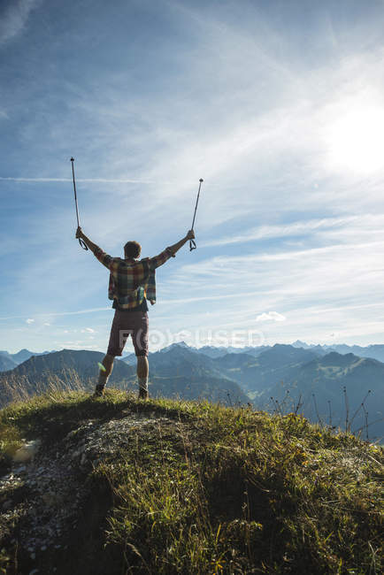 Austria, Tirol, Tannheimer Tal, joven animando en la cima de la montaña - foto de stock