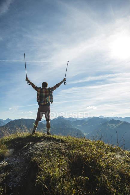 Austria, Tyrol, Tannheimer Tal, young man cheering on mountain top — Stock Photo