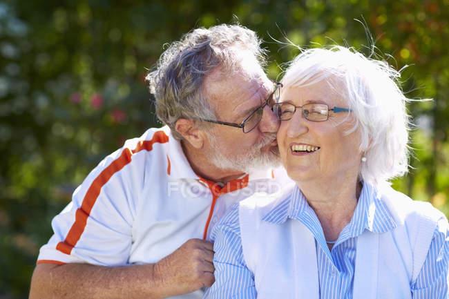 Старший мужчина целует жену в парке — стоковое фото