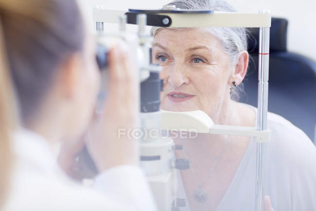 Eye doctor examining senior woman's vision — Stock Photo