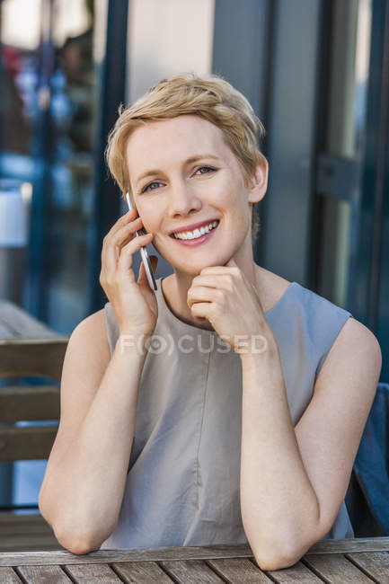 Portrait of smiling blond woman telephoning with smartphone — Stock Photo