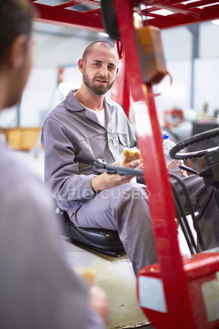 Worker on forklift in factory having lunch break talking to another worker — Stock Photo