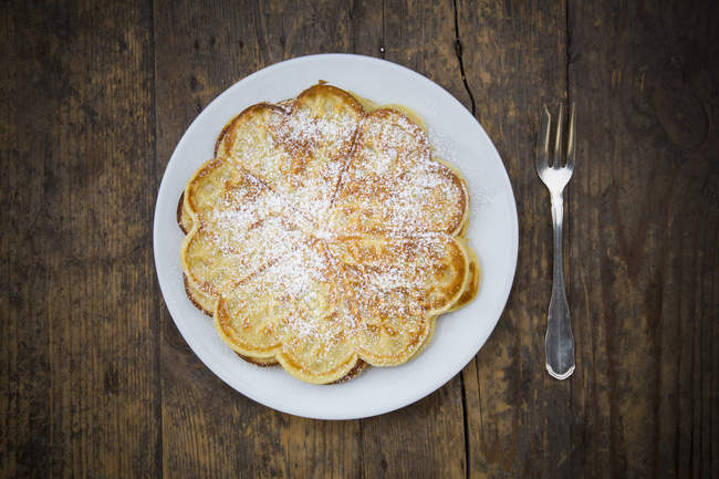 Вафель посыпают пудрой сахара на темное дерево — стоковое фото