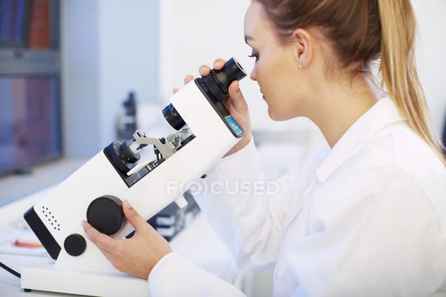Female Optometrist looking through microscope — Stock Photo