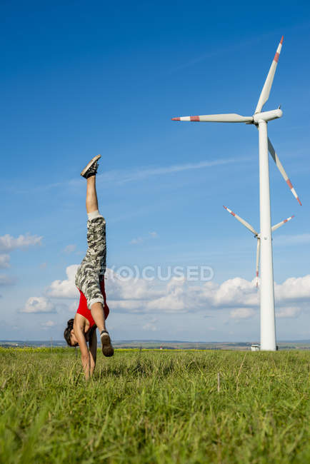 Sportive young woman doing handstand on filed path with wind turbines — Stock Photo