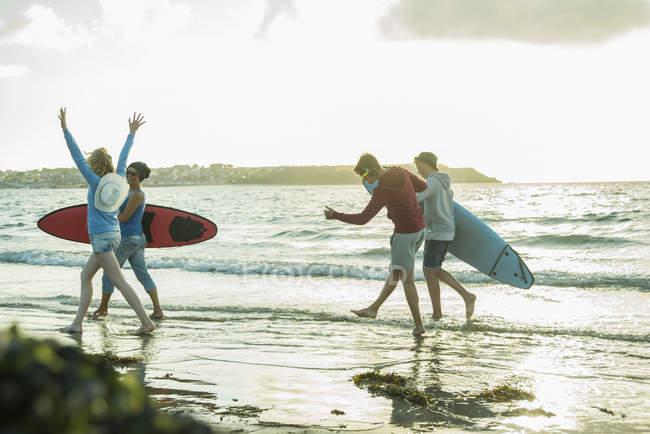 Frau und drei Teenager mit Surfbrettern am Ufer des Meeres — Stockfoto