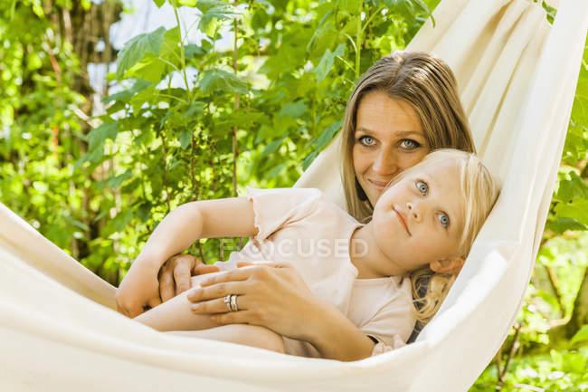 Madre e figlia rilassarsi in amaca all'aperto — Foto stock