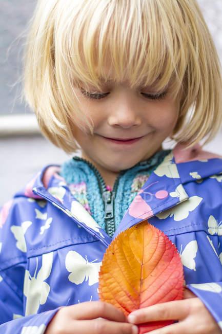 Маленькая девочка держит осенний лист — стоковое фото