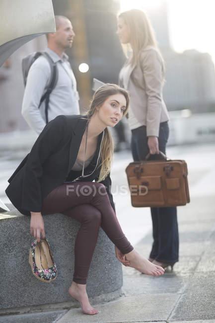 Деловая женщина расслабляющий без ее обувь, коллеги на фоне — стоковое фото