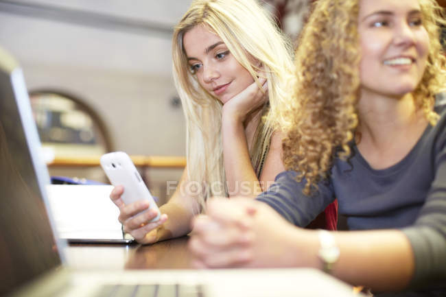 Две студентки с мобильным телефоном и ноутбуком в библиотеке — стоковое фото