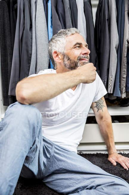 Hombre sonriente sentado en el suelo de su vestidor - foto de stock