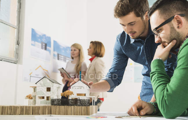 Young architects in office looking at architectural model — Stock Photo