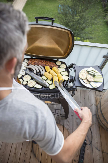 Человек жарит барбекю на своем балконе — стоковое фото