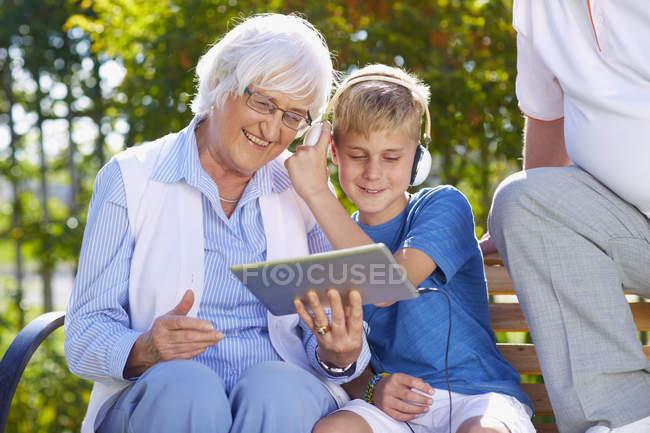 Nieto y abuelos con tableta digital en el Parque - foto de stock