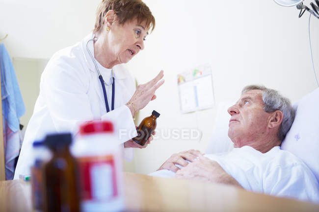 Doctor talking to senior man in hospital bed — Stock Photo