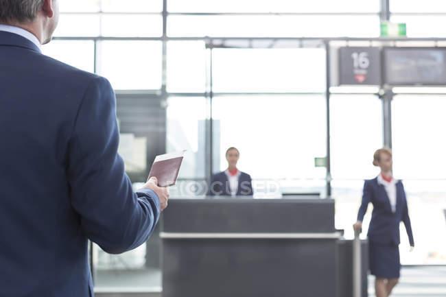 Empresario con tarjeta de embarque y pasaporte en el aeropuerto - foto de stock