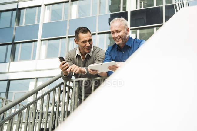 Два бизнесмена стоят перед офисным зданием с помощью мобильного телефона и цифрового планшета — стоковое фото