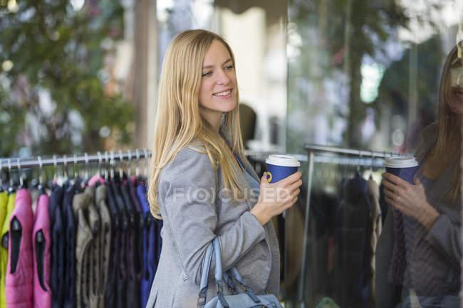 Lächelnde junge Frau beim Coffee to go einkaufen — Stockfoto