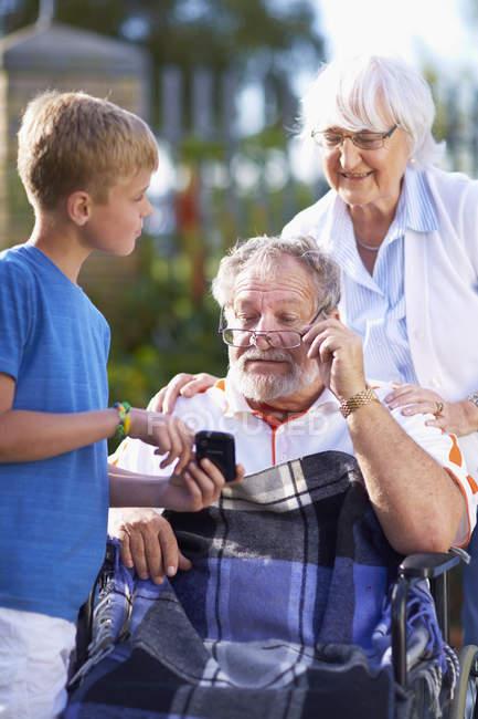 Бабушка и внук, объясняя сотовый телефон к деду в инвалидной коляске — стоковое фото