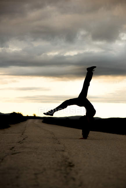 Silhouette of young sportive woman doing handstand on an empty road by twilight — Stock Photo