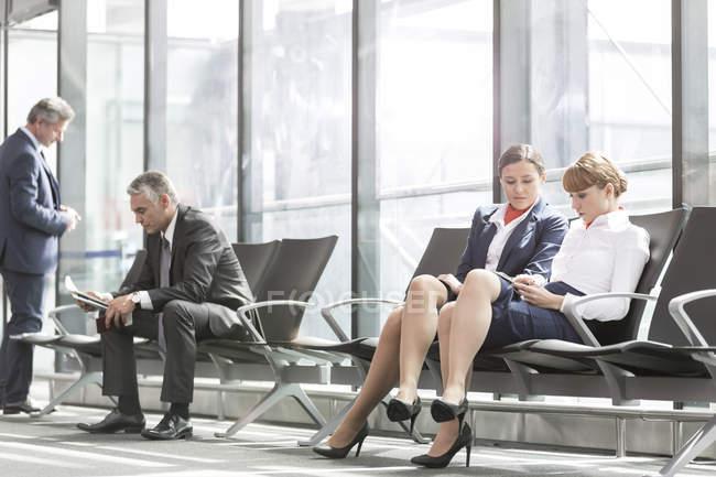 Dos asistentes de vuelo y los empresarios en el salón de la salida de aeropuerto - foto de stock